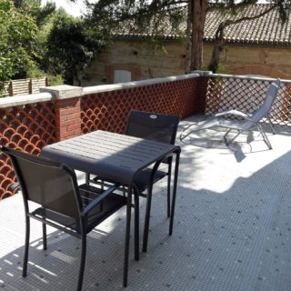 Large private terrace of suite fire with garden table and deck chairs, view on the park and swimming pool