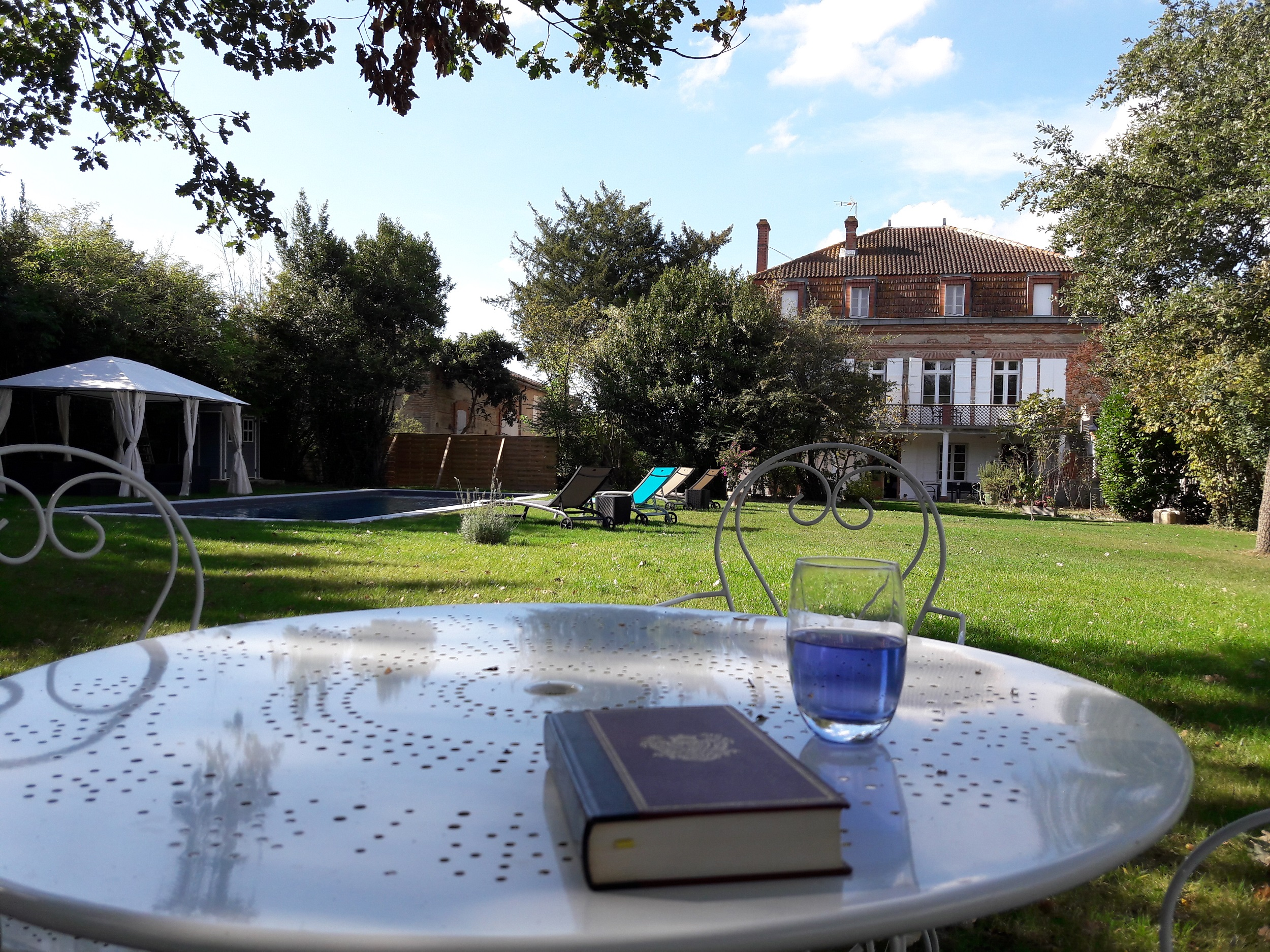 Parc avec salon de jardin pour un moment de détebte avec un livre ou une boisson avec vue sur la piscine