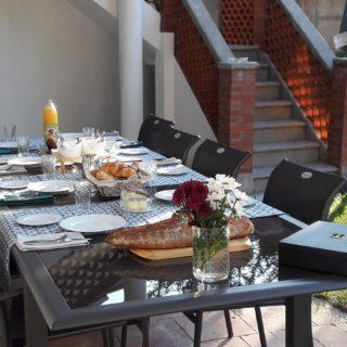 Table du petit-déjeuner servi en terrasse avec du pain et des viennoiseries, jus de fruits du Tarn et Garonne