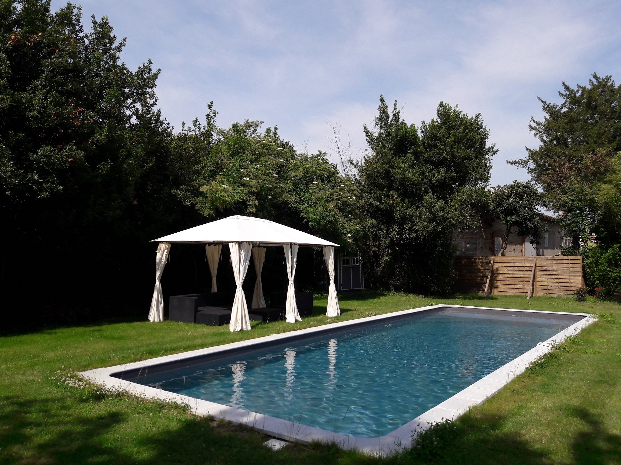 Grande piscine avec plage de détente et salon de jardin