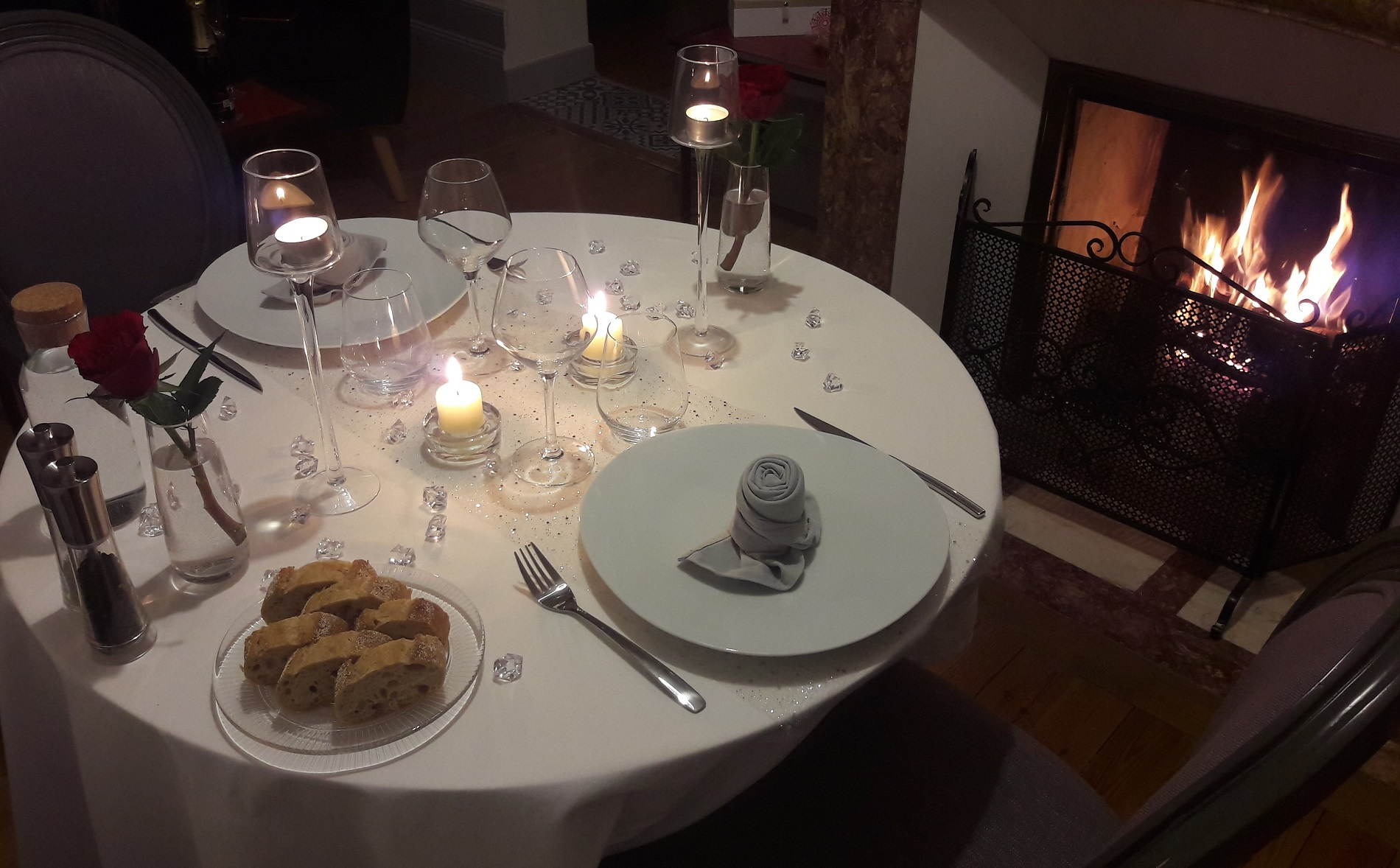 Elegant table with quality plates and glasses, romantic setting with candles and fireplace