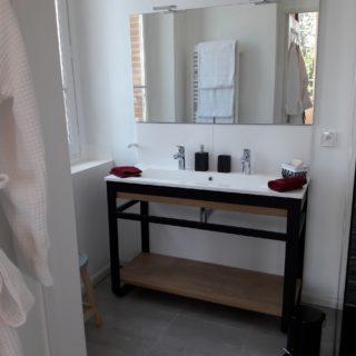 Salle de bain haut de gamme avec double vasque, douche à l'italienne et peignoirs