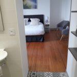 Salle d'eau ouverte sur la chambre avec beau parquet