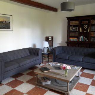 Salon de détente de la maison d'hôtes avec canapé et bibliothèque