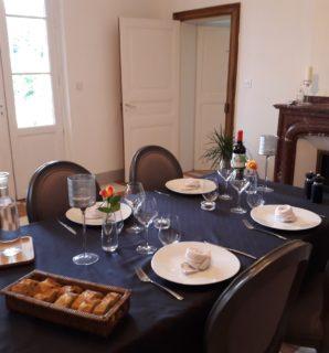 Table d'hôtes raffinée servie dans la salle à manger près du feu de cheminée
