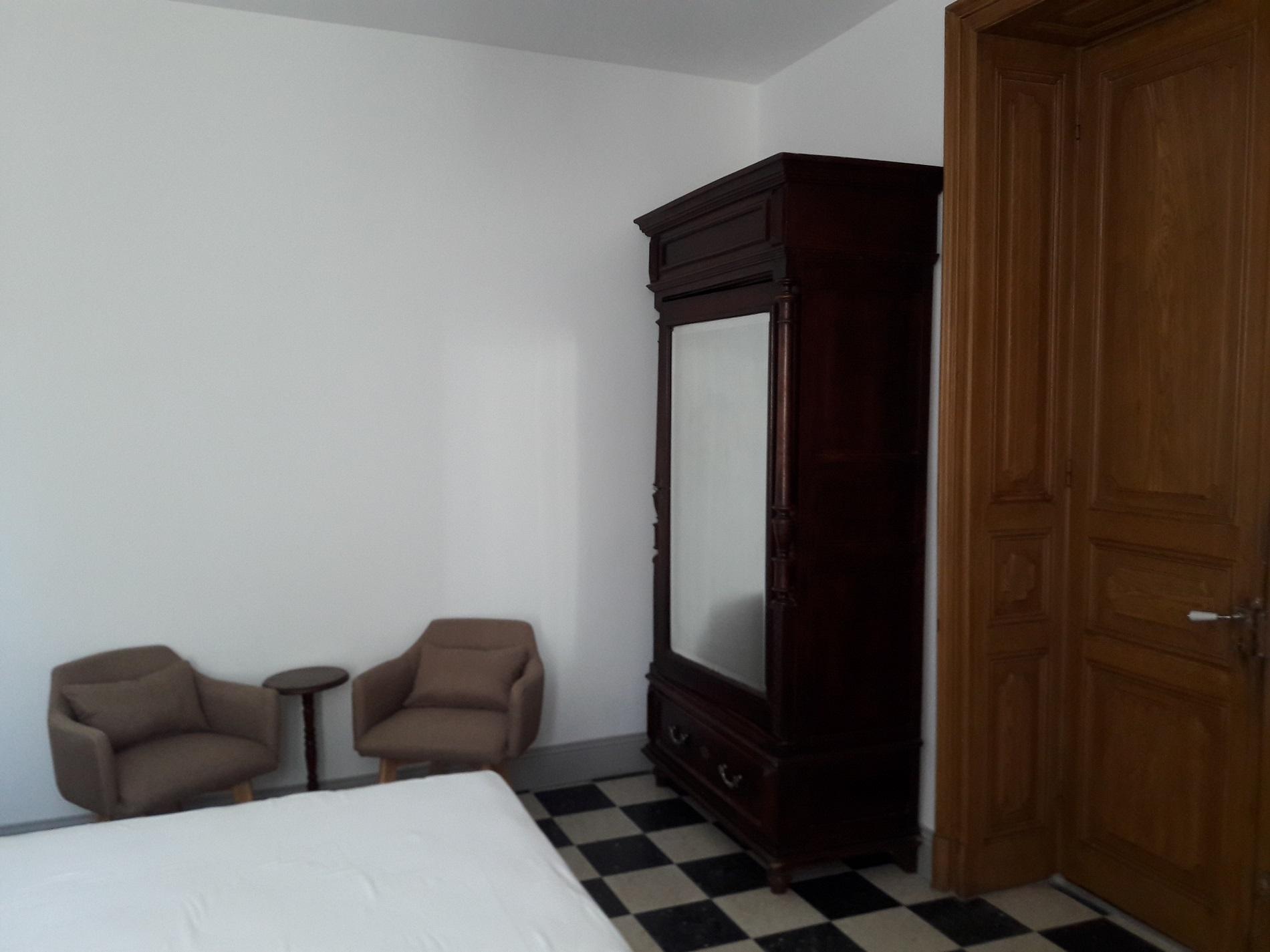 Chambre avec armoire et fauteuils de détente
