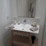 Bathroom suite Quintessence with modern washbasin, beige towels, organic toiletries