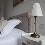 Beautiful renovated bedside table and its vintage bedside lamp, refined beige bedhead