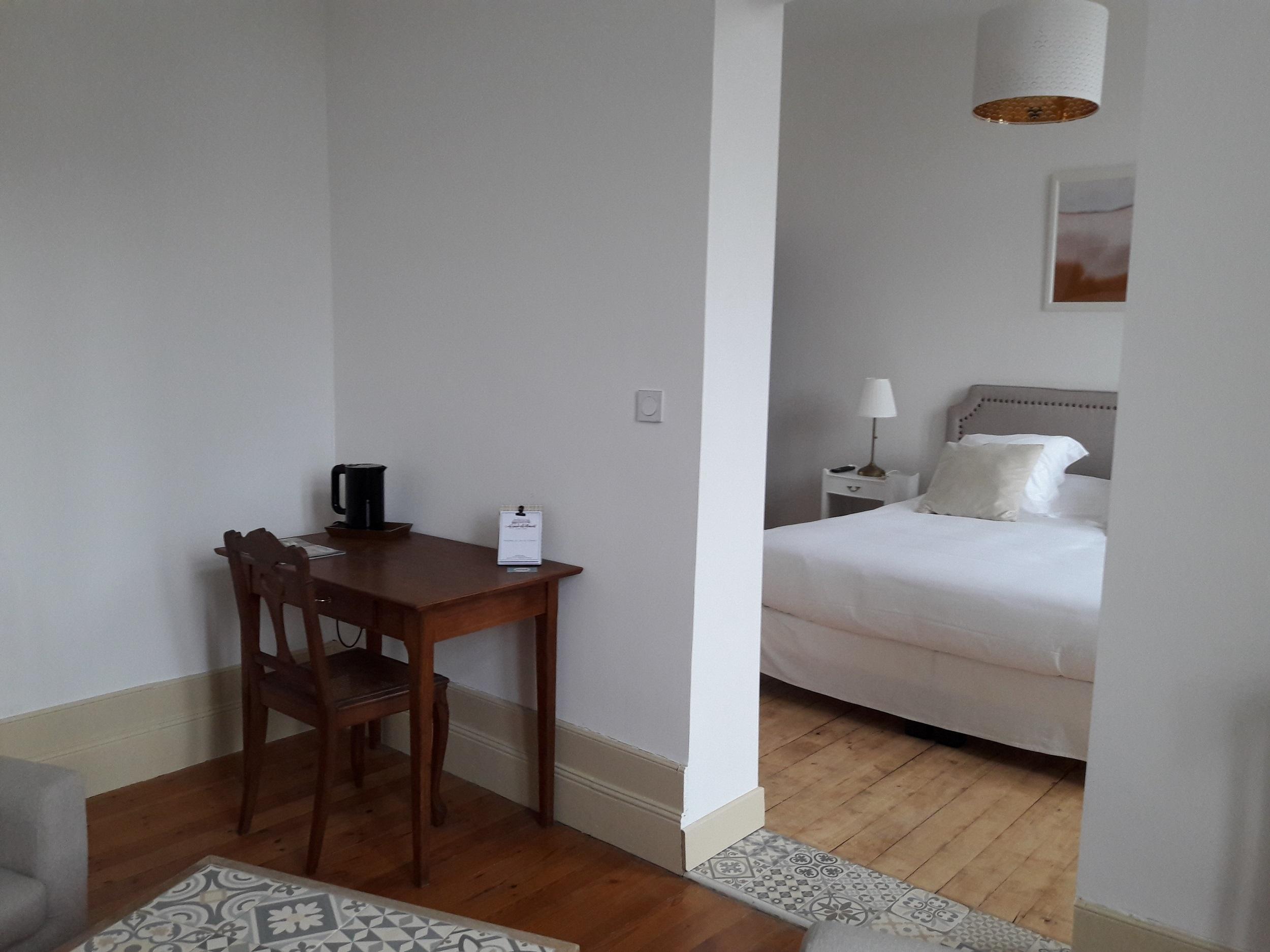 Bureau dans le salon de la suite avec bouilloire, jolie chaise ancienne, ouverture sur la chambre