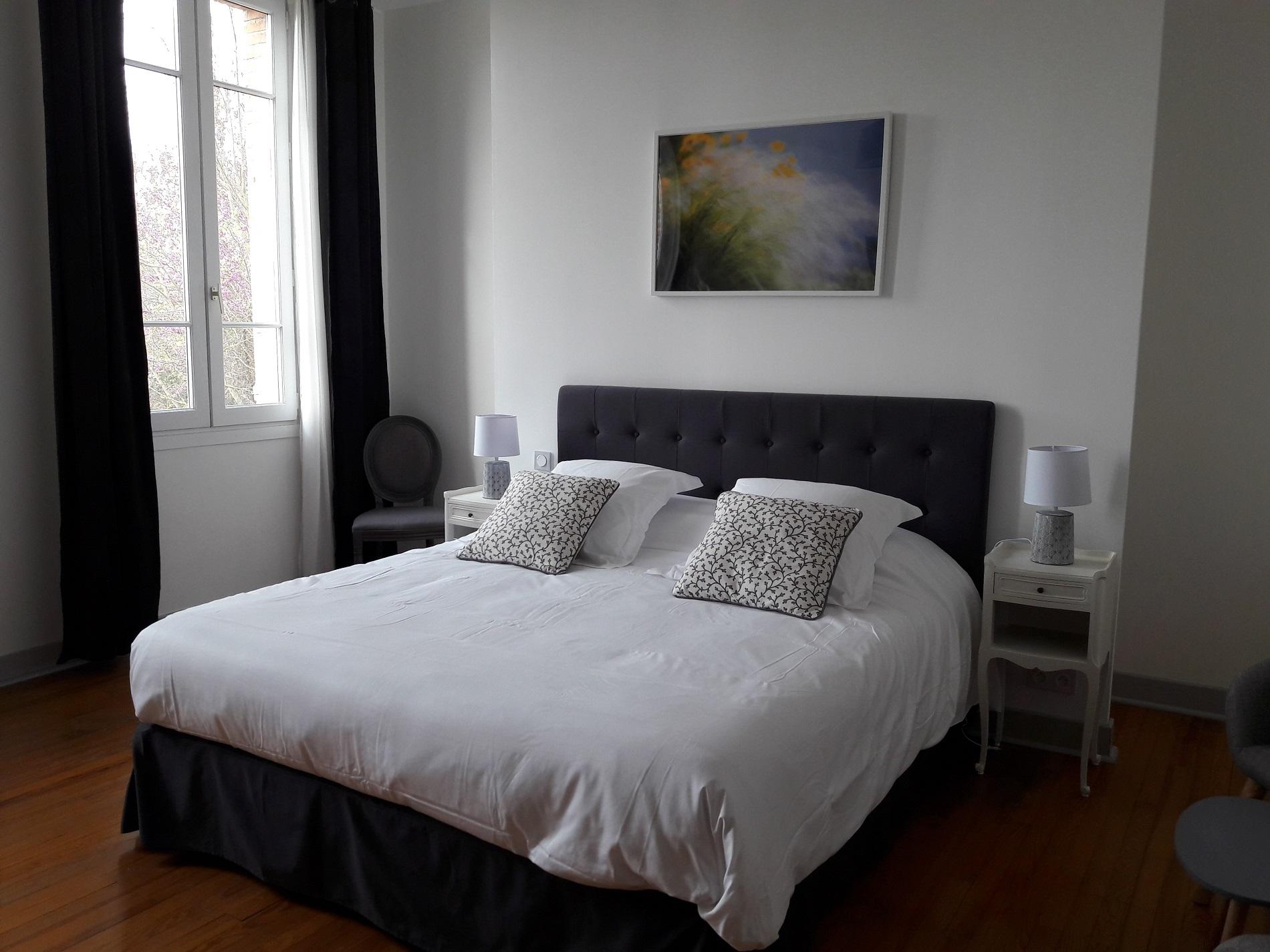 Belle chambre d'hote avec lit king size et literie de grand confort, décoration dans les tons de gris sur le thème de l'air
