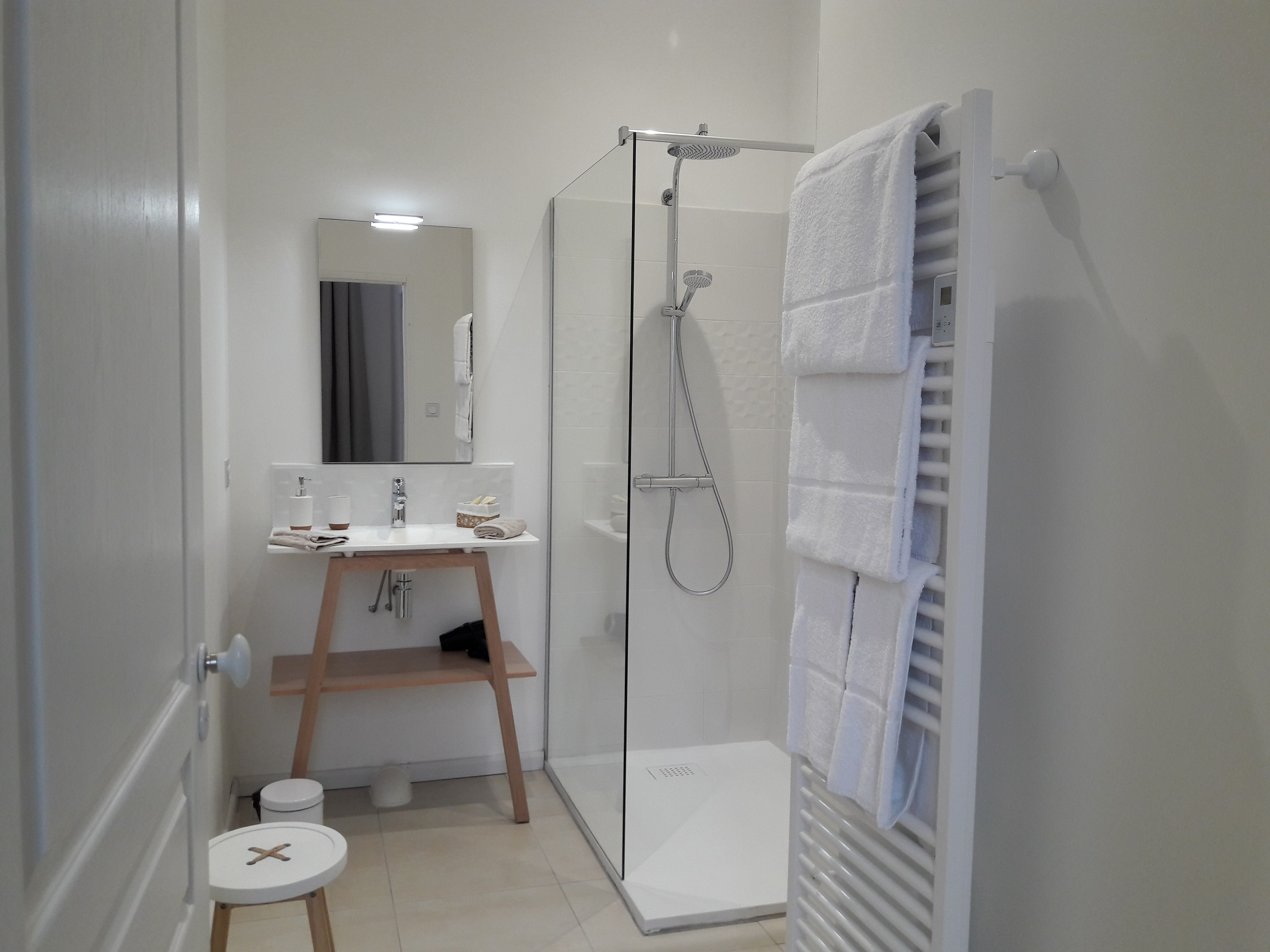Salle de bain à la décoration épurée dans les tons de blanc, vasque moderne avec produits de douche bio, douche à l'italienne et serviettes de qualité