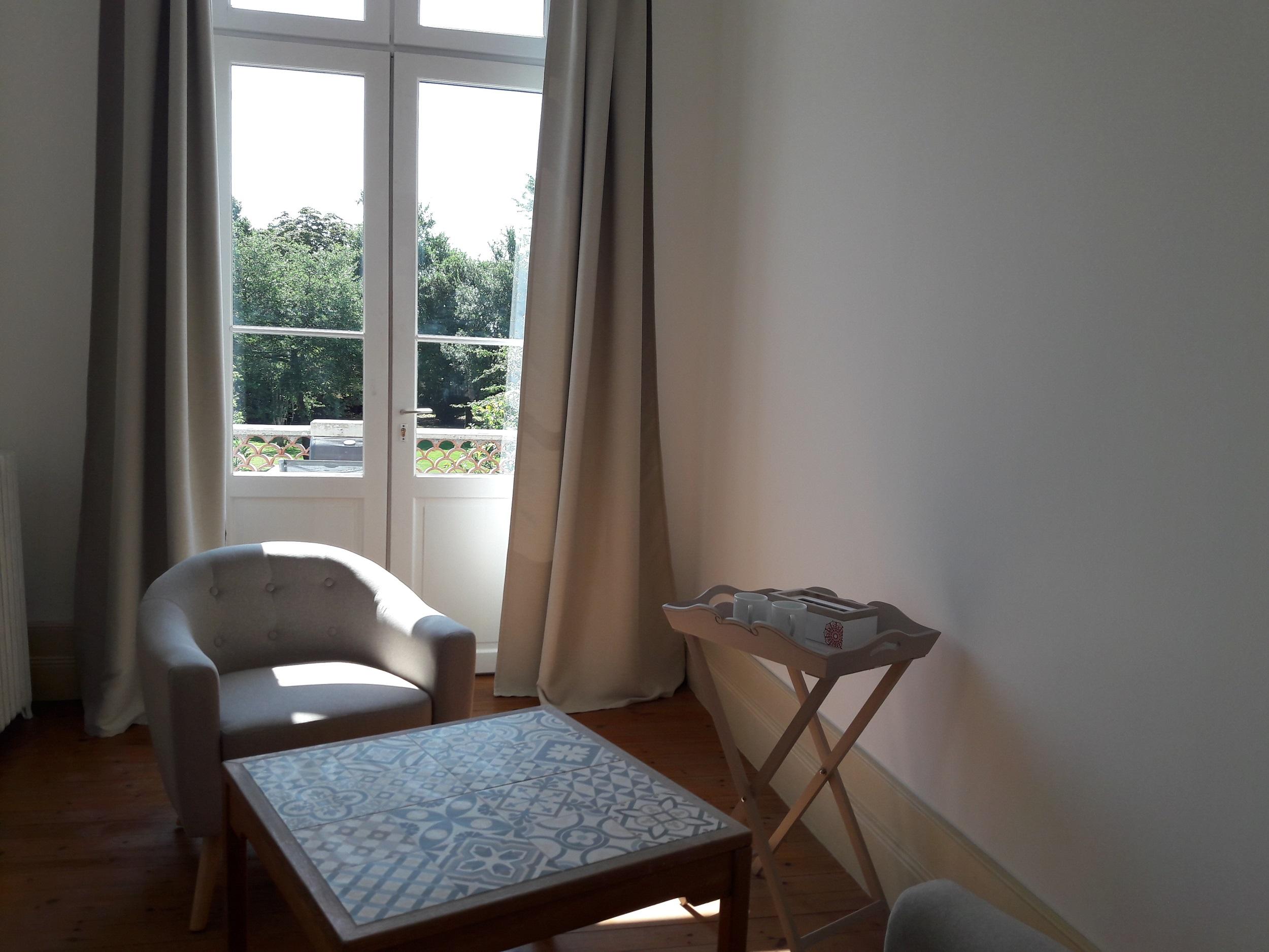 Salon privatif de la suite avec fauteuils modernes, table basse et accès sur la terrasse privative avec vue sur le jardin