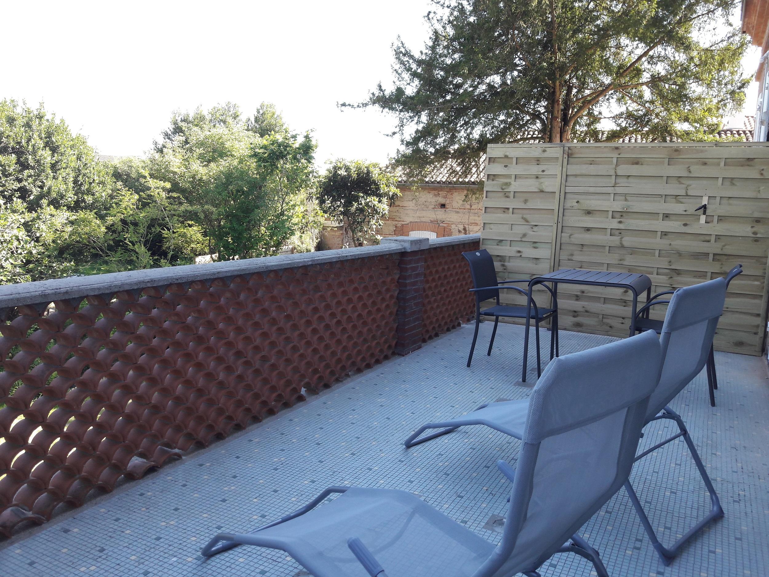 Terrasse privative de la suite quintessence pour se détendre avec transats, table et chaises et une belle vue sur le jardin