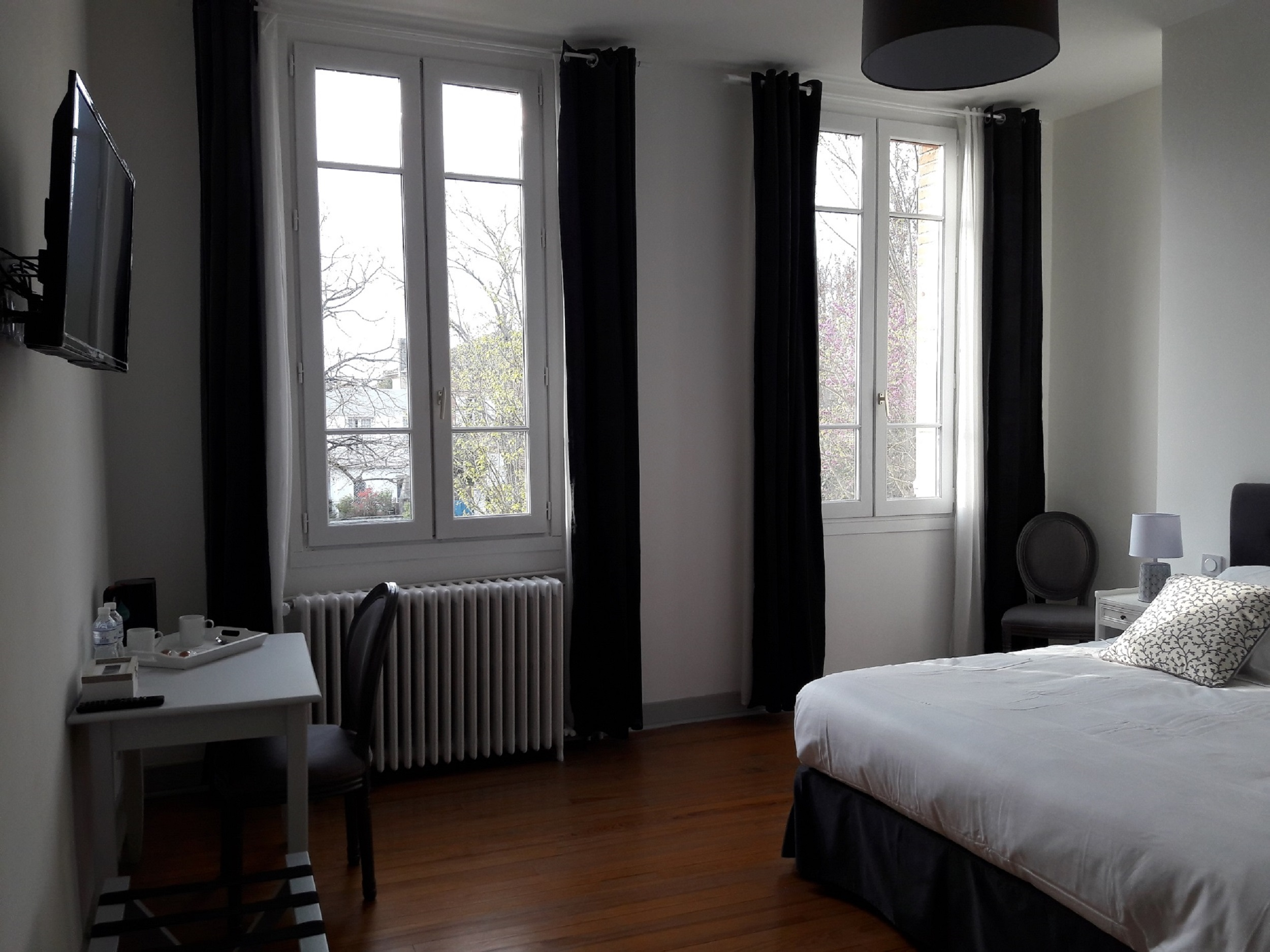 The large windows of the guestroom with their with their large grey velvet curtains overlook the village, charm of the old with the beautiful original wooden floor