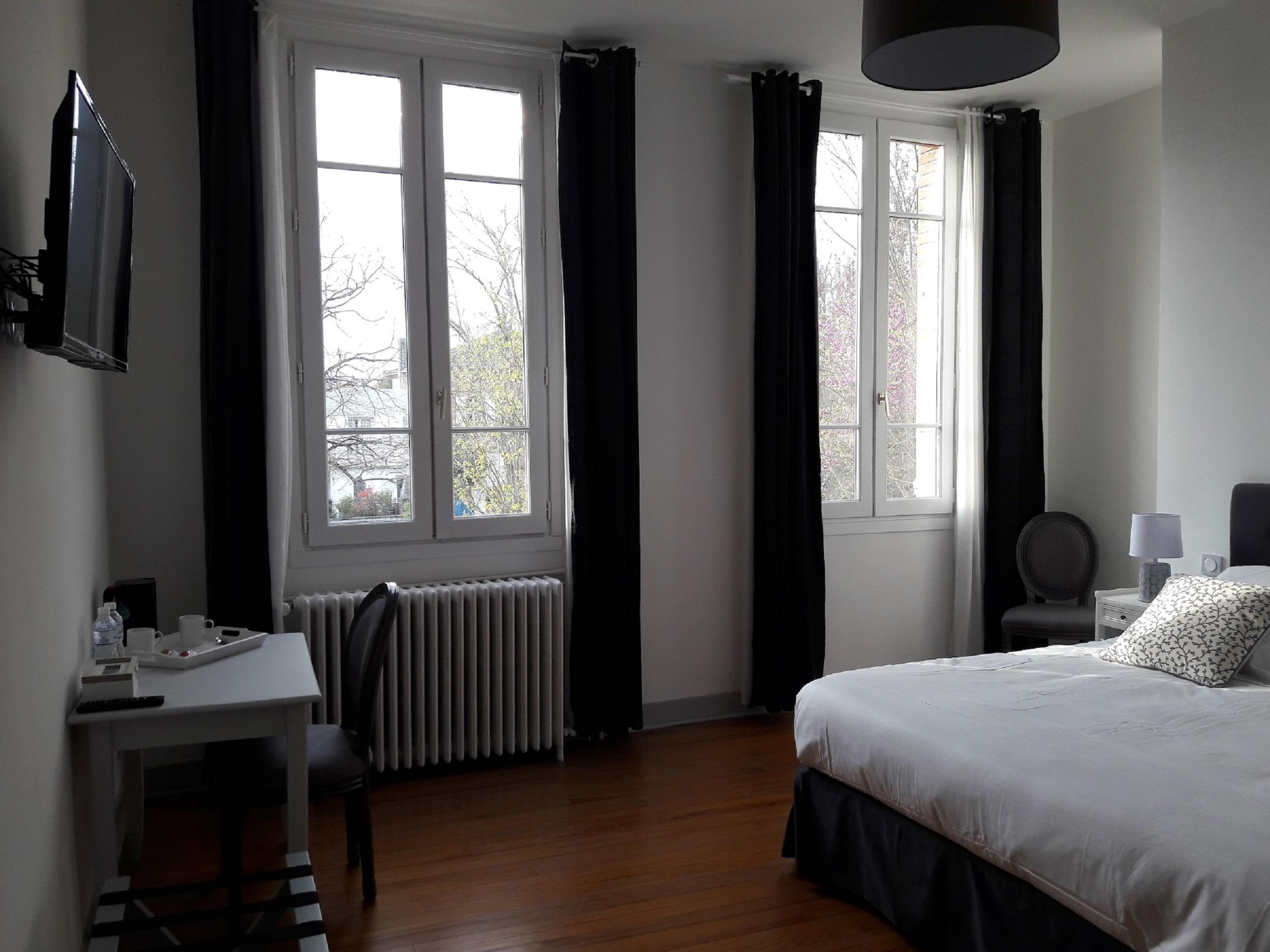 Les grandes fenêtres de la chambre d'hotes et leurs grands rideaux gris en velours donnent sur le village, le charme de l'ancien avec le beau parquet d'origine