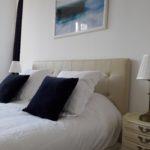 Suite Eau à la décoration raffinée avec des oreillers moelleux, une tête de lit capitonnée beige et un cadre photo sur le thème de l'eau