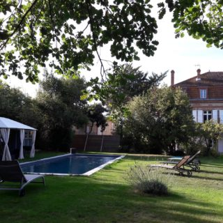 Piscine dans le parc des chambres d'hôtes avec salon de jardin pour se détendre sous l'ombre de la tonnelle