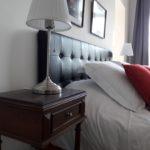 Très beau lit de la suite Feu avec son chevet ancien, sa lampe de chevet vintage et ses oreillers moelleux