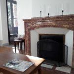 Salon cosy privé de la suite Feu avec belle cheminée en marbre, fauteuils et table basse pour lire un magazine