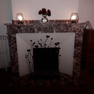 Ambiance romantique autour de la cheminée de la chambre d'hôtes Feu avec roses rouges et lumière tamisée