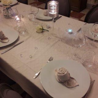 Dressage raffinée du dîner en table d'hôtes avec des assiettes et des verres de qualité et une serviette en forme de rose