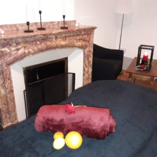 Nicely decorated massage table in a lounge with fireplace