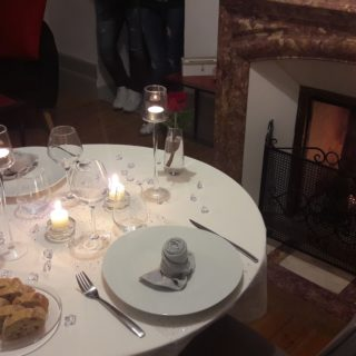 Nicely dressed table by the fireplace for a romantic dinner