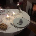 Beautiful romantic table setting with pretty plates and glasses, candles, flowers and open fire