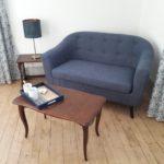 Salon de la suite Eau avec canapé bleu moderne, petite lampe et plateau de courtoisie posé sur une table basse ancienne