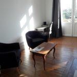 Salon cosy avec deux fauteuils noirs, une table basse ancienne en bois, un beau bureau, du parquet et une grande porte fenêtre donnant sur la terrasse