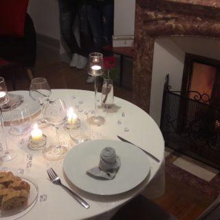 Belle table dressée devant le feu de cheminée pour un dîner romantique