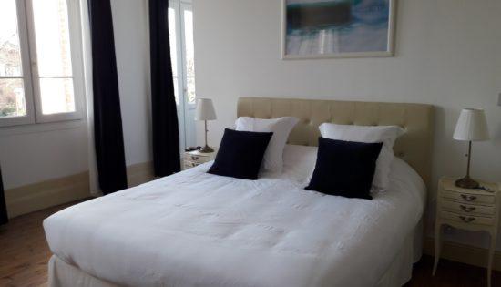 Lit king size très confortable de la suite Eau avec oreillers moelleux, joli cadre photo évoquant l'eau