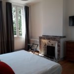 Belle chambre avec cheminée en marbre et grande fenêtre avec belles tentures donnant sur la terrasse