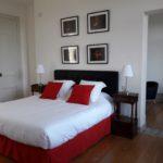 Belle chambre dans les tons de rouge avec tête de lit noire, cadres photos, chevets et beau parquet anciens