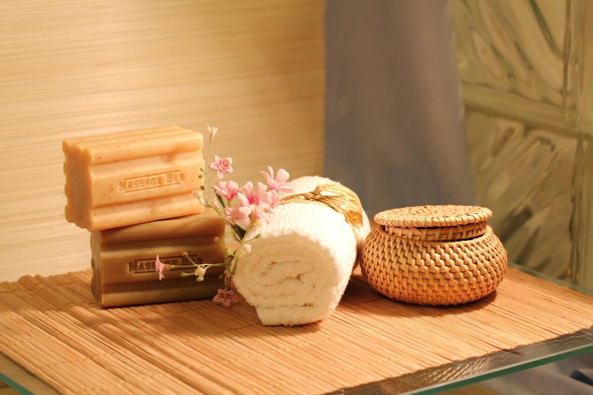 Une jolie décoration pour une table de massage avec serviette douce, fleurs et savons
