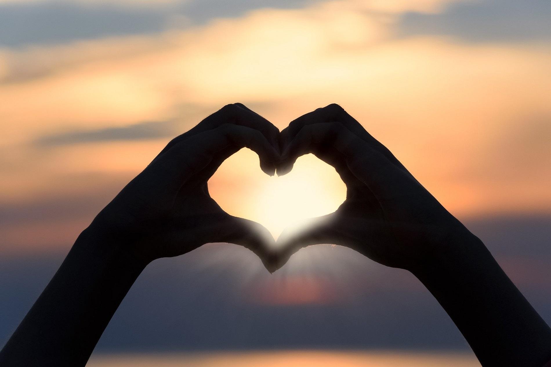 Mains en forme de coeur devant un coucher de soleil romantique